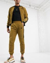 Sik Silk Siksilk Nylon Joggers In Gold With Logo Side Stripe