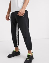 Reebok Training Woven Joggers With Logo Taping In Black